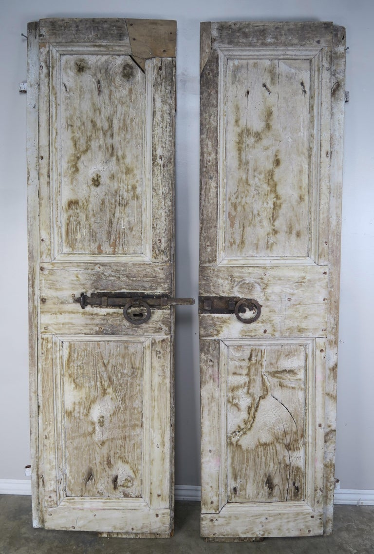 Pair of rustic Swedish distressed white painted doors with original heavy wrought iron hardware. Beautiful distressed finish with wood exposed underneath.
