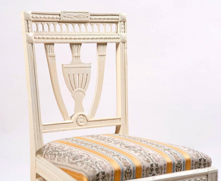 A charming pair of cream-colored, Swedish-Gustavian painted chairs with neoclassical decorative elements that include a carved urn-design on center back, carved gallery along the crest rail, and carved festoons hanging from the carved apron. Chair