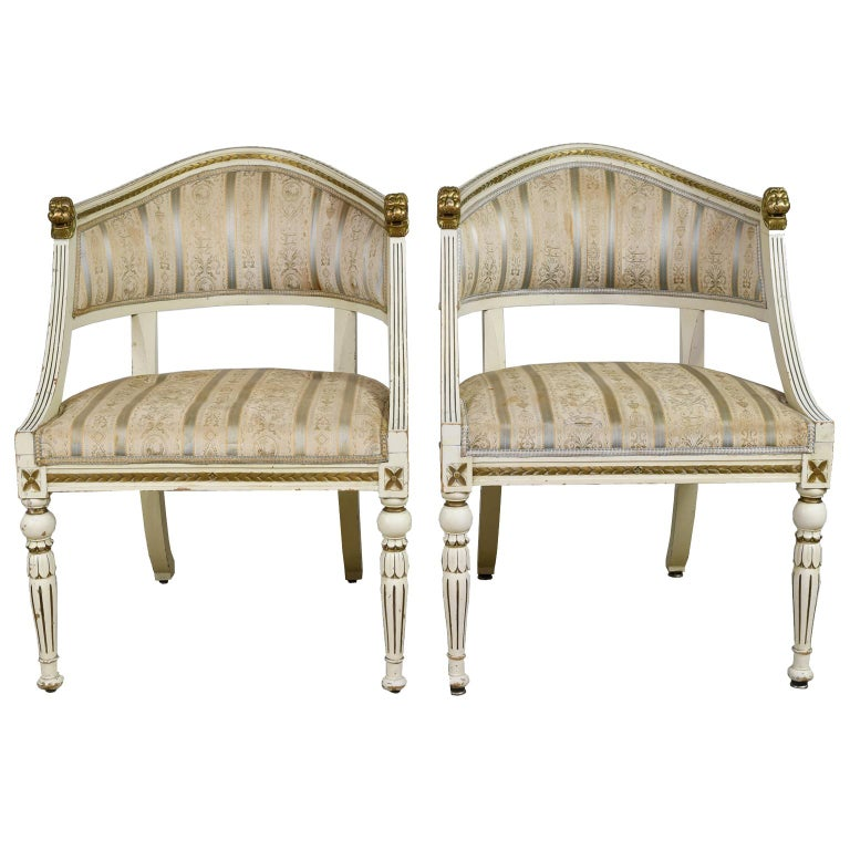 A very handsome pair of Gustavian-style armchairs with upholstered seat and back. Frame is painted an ivory color with antique gold accents and features a gondola form with arched back, carved lions heads at each end of the crest rail which has a