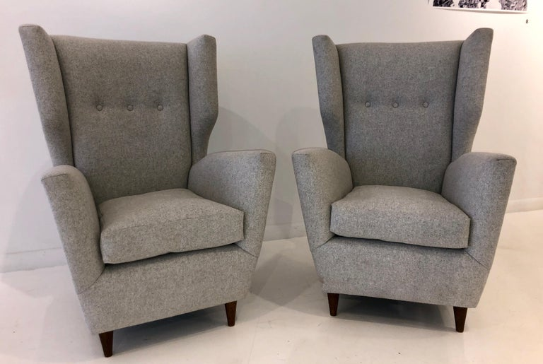 Exaggerated wingback lounge chair with sharp tailoring and generous proportions, on tapered walnut legs and upholstered in a light gray felt wool.