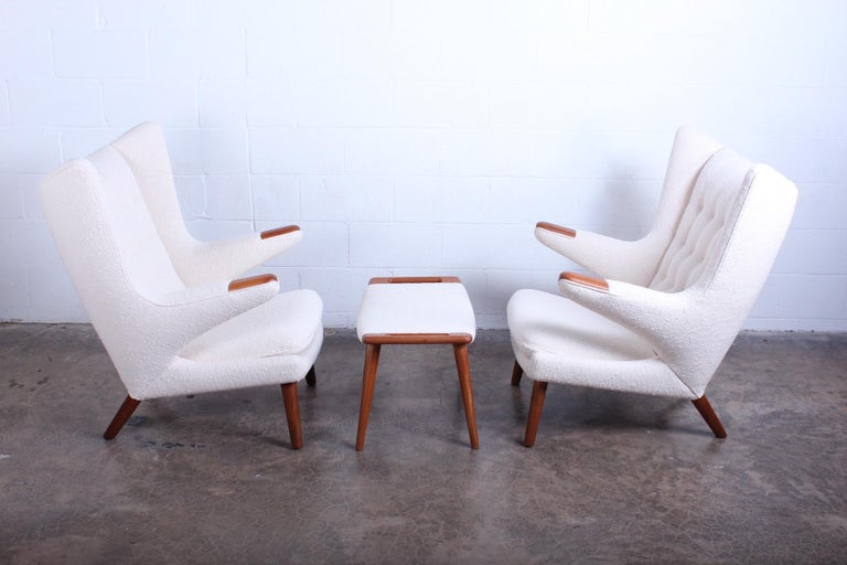 A pair of papa bear chairs and ottoman designed by Hans Wegner for AP Stolen. One chair and ottoman retain their original stamp. Fully restored and upholstered in holly hunt fabric.