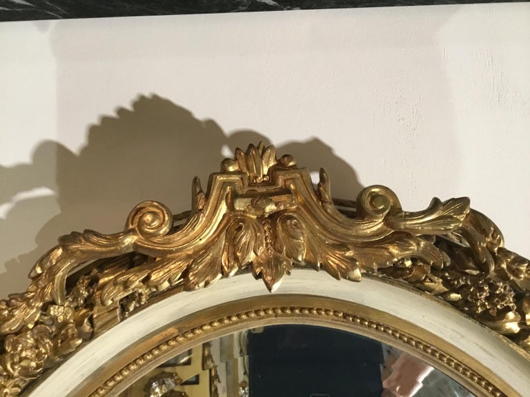 French Pair of Parcel Paint and Parcel Gilt Beveled Oval Mirrors, with Bird Carvings For Sale