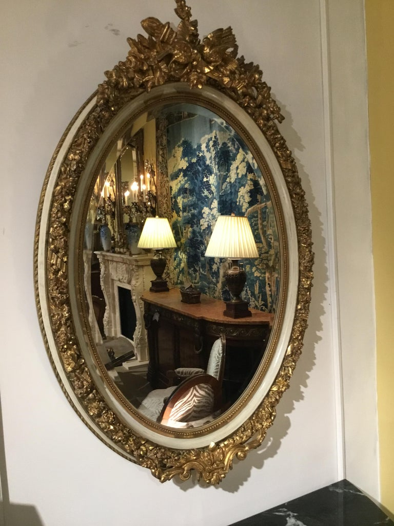 Pair of Parcel Paint and Parcel Gilt Beveled Oval Mirrors, with Bird Carvings For Sale 1