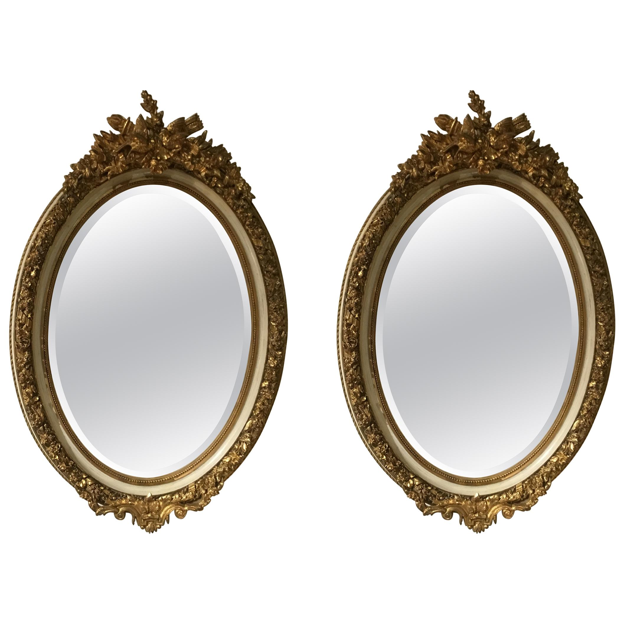 Pair of Parcel Paint and Parcel Gilt Beveled Oval Mirrors, with Bird Carvings