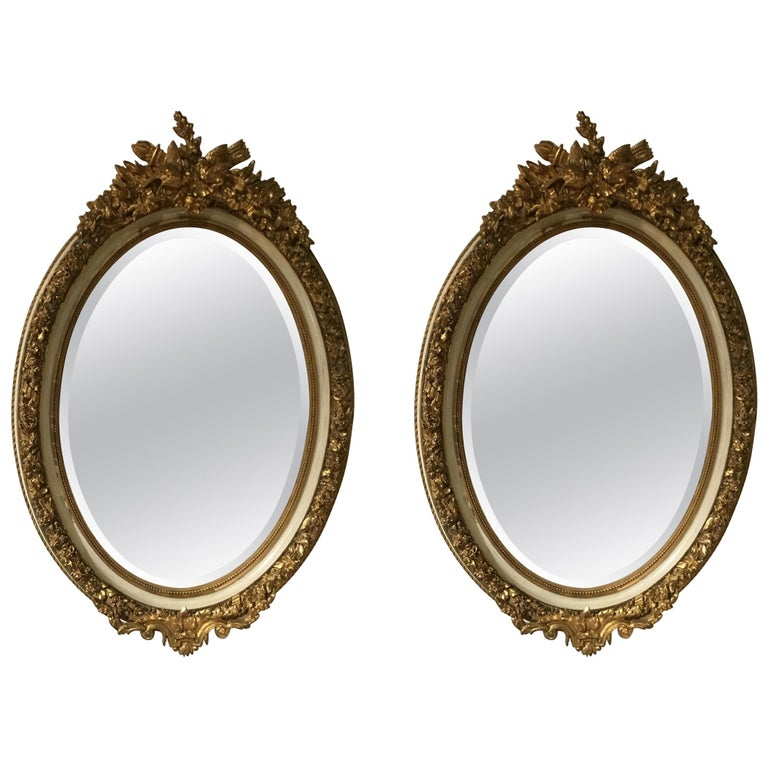 Pair of Parcel Paint and Parcel Gilt Beveled Oval Mirrors, with Bird Carvings For Sale