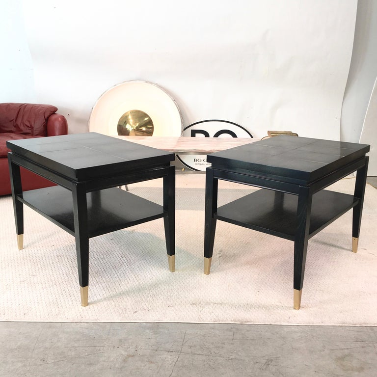 Pair of 1950s well-proportioned rectangular two-tier side or end tables in the style of Tommi Parzinger, stained black with transparent finish highlighting the grained wood with brass tone metal inlay and sabots on four square tapered legs. Lower
