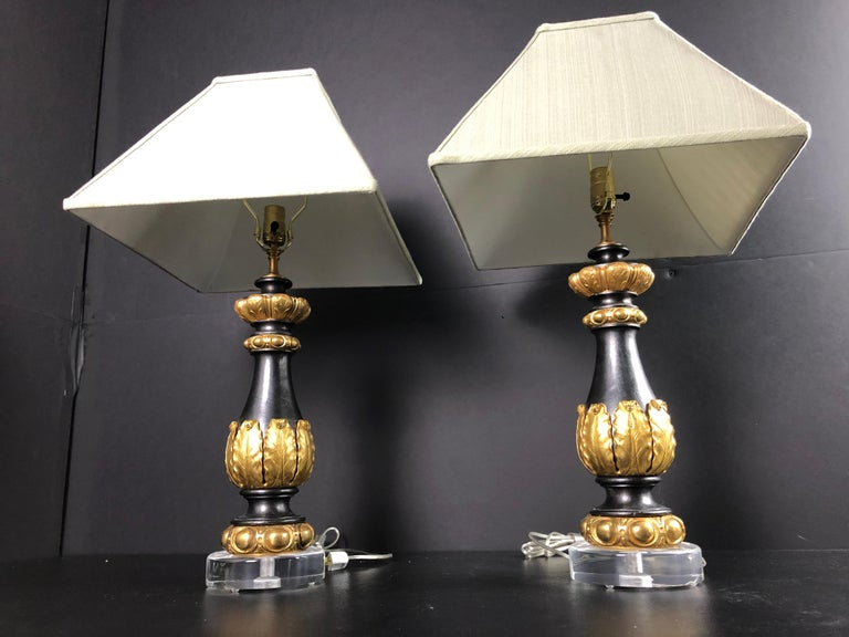 Pair of patinated and gilt bronze garnitures as lamps. A pair of bronze doré mounted baluster form iron garnitures mounted as lamps on round Lucite bases. Green linen shades included.