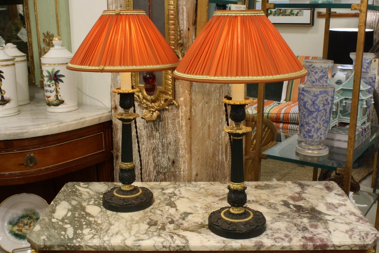 Pair of handsome 19th century French gilt bronze and patinated bronze candlesticks in the restoration style. The candlesticks have been wired as lamps and fitted with pleated orange silk shades with trim and