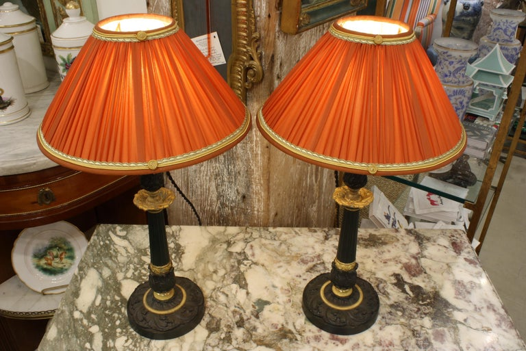 French Pair of Gilt and Patinated Bronze Candlestick Lamps with Orange Silk Shades For Sale