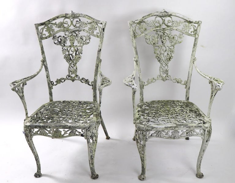 Wonderful pair of cast aluminum garden or patio chairs, with exceptionally patinated surface. Classical grape and cable motif armchairs, both are structurally sound and sturdy, one is missing some of the metal frame edge, from seat, as shown.