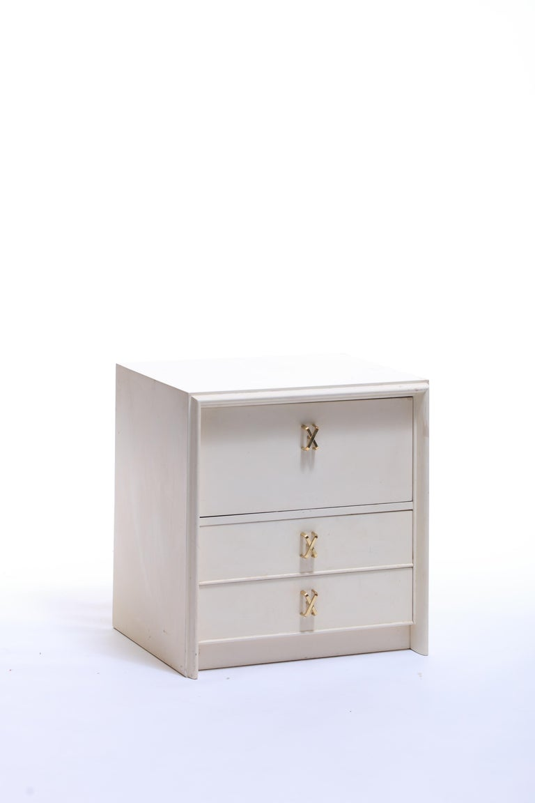 Mid-20th Century Pair of Paul Frankl Ivory Lacquered Night Stands with Brass X Pulls, circa 1950 For Sale