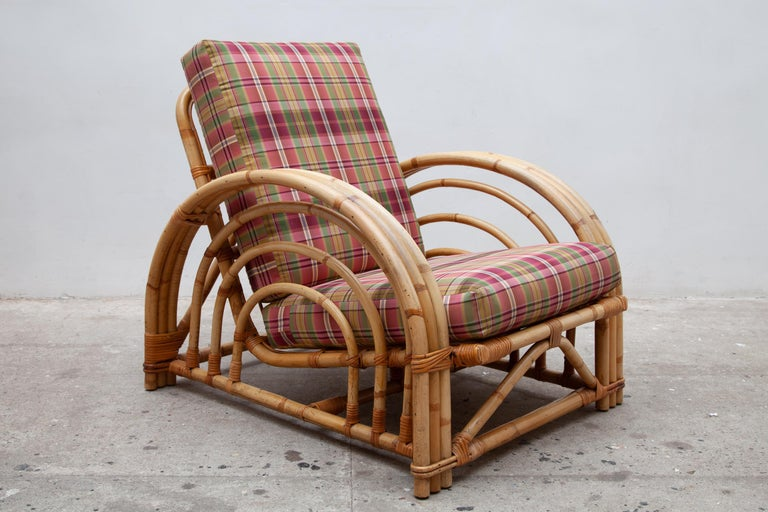 A pair of bend bamboo lounge chairs in the style of Paul Frankl. Features sculptural circular armrests and colorful plaid cushions. This Art Deco-inspired set retains a timeless style that would look great in any modern space. This lightweight yet