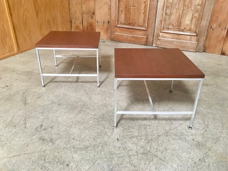 A pair of walnut tops with aluminium base side tables from the Erwin collection designed by Paul McCobb for Calvin furniture.