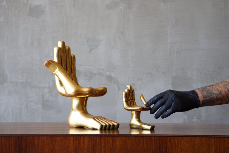 Incredible pair of 'Hand Foot' sculptures in gold leaf coated wood by Mexican artist, Pedro Friedeberg.   Excellent table top sizes with a rich and warm patina. Minor nicks to finish on middle and index finger tips of larger piece, as