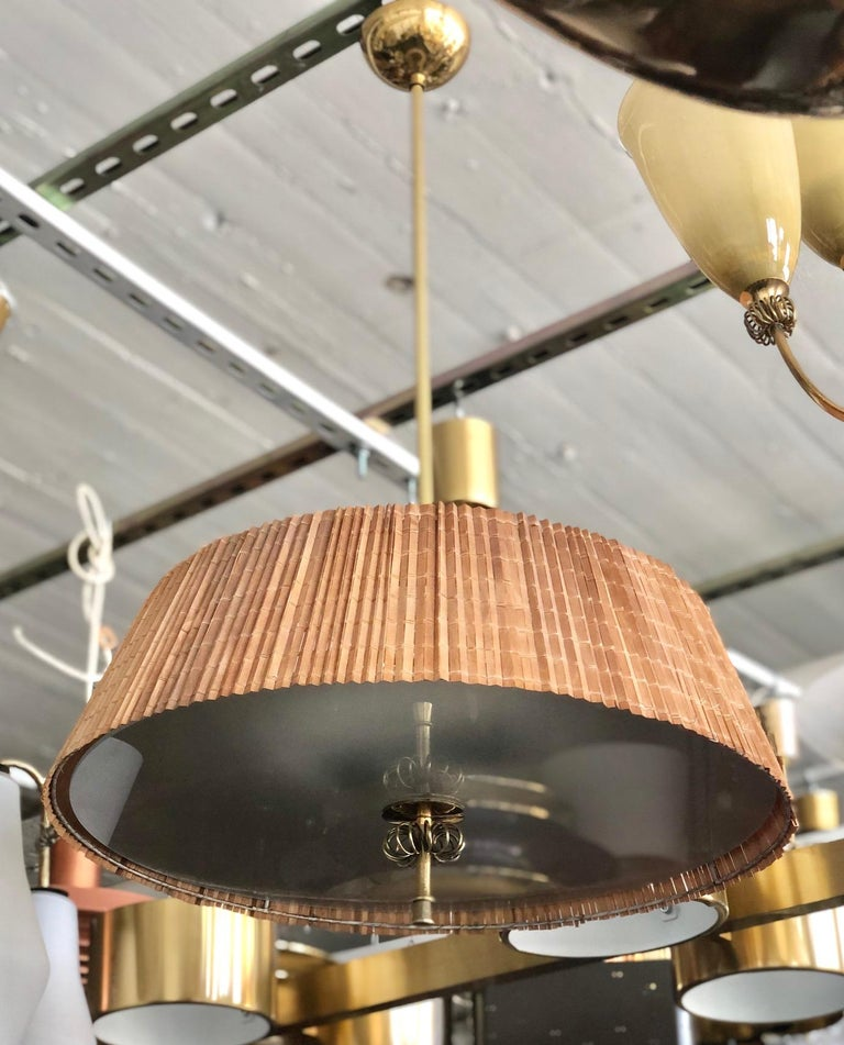 A pair of custom order wood stripes and brass ceiling lights with long stems designed by Paavo Tynell for the interior of Hok Elanto in Helsinki, from the 30's/40's. Overall drop can be adjusted. Rewiring available upon request. Can be sold