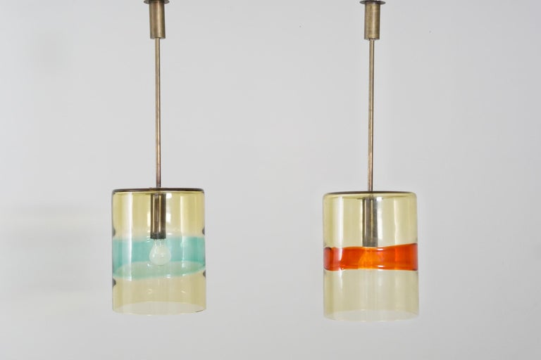 Beautiful pairs of pendants by Flavio Poli, made of hand blown glass with a light green tint and colored stripes in orange and turquoise. Brass mounting. Manufactured by Seguso Vetri D'Arte Murano. Originally part of the interior of Hotel Royal in