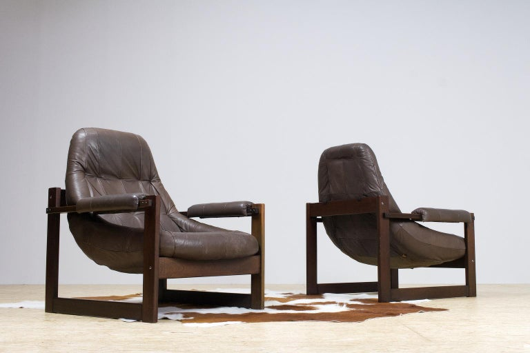 Great set of matching leather lounge chairs by Percival Lafer, 1960-1970s Brazilian modern. The massive wooden cubical frame holds the 'floating' dark brown leather shell. The hard wooden construction draws the most attention, which is a typically
