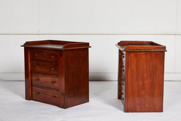 19th century charming English pair of miniature mahogany four-drawer chests with gallery lined tops and wooden knobs.