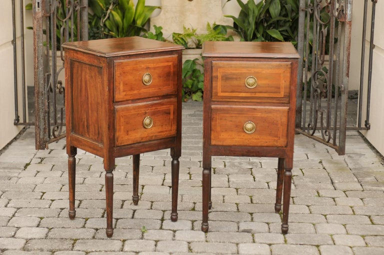 A pair of petite Italian walnut two-drawer commodes from the early 19th century with crossbanded inlay and turned legs. Each of this pair of small Italian commodes features a rectangular top, adorned with a delicate crossbanded inlay and beveled