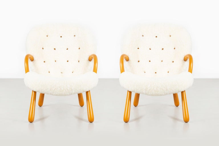 "Set of two clam chairs   designed by Philip Arctander   circa 1940s  freshly reupholstered in shearling + wood   Measures: 33 ?"" H x 26 5/16"" W x 29 ?"" D x seat 15 13/16"" H."