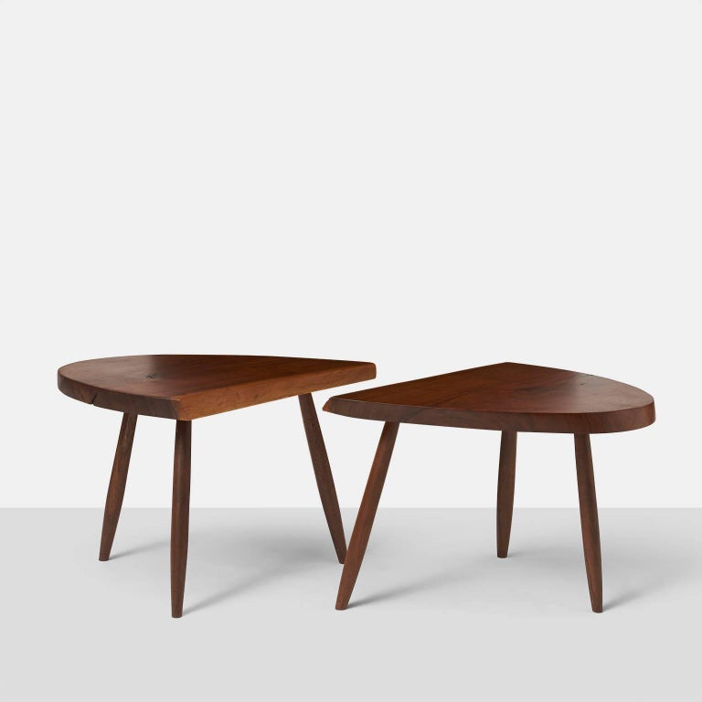 An elegant pair of studio crafted walnut coffee tables with eased edge by American woodworker Phillip Lloyd Powell. These triangular tables are in an excellent condition. Measurement is for each piece.