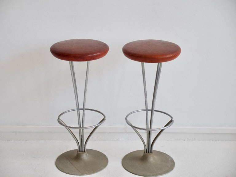 Pair of high bar/kitchen stools with chrome-plated metal frame, mounted on round aluminum foot, seat originally upholstered in cognac-colored leather. Designed in 1961 by Piet Hein. Produced by Fritz Hansen. Literature: Noritsugu Oda. Danish