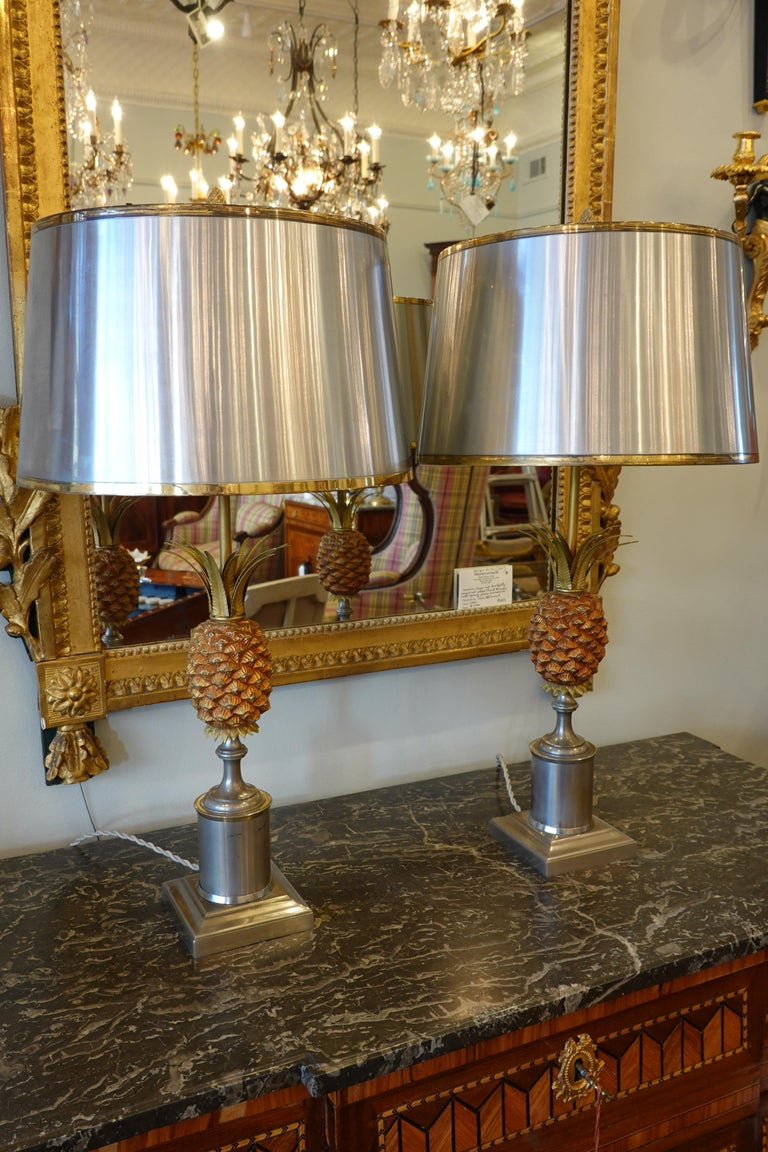 Pair of brushed steel lamps featuring a pineapple and steel shade in the style of Maison Jansen or Maison Charles. The shade is brushed steel to match the lamp base with brass trim, and has a stylized pine cone finial. The lamps have been rewired