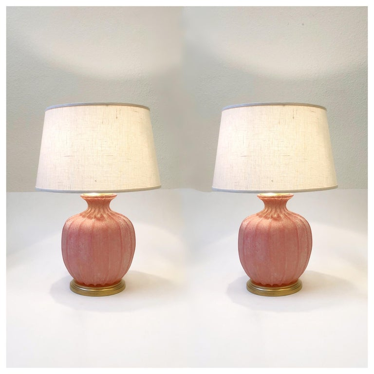 A pair of 1970s Italian pink Scavo Murano glass and satin brass table lamps by Seguso Vetri d'Arte. The lamps have been newly rewired and have new vanilla linen shades. The hardware is satin brass and the base is gilded wood. Both lamps are signed
