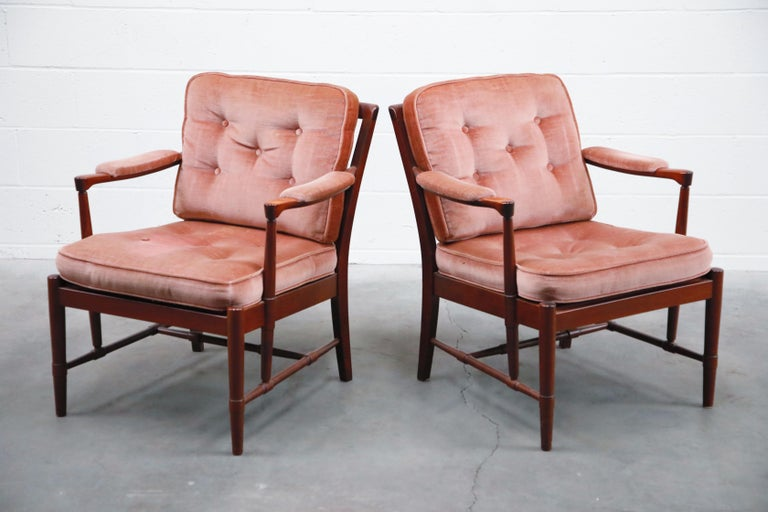 An incredible pair of Danish modern rosewood and pink velvet armchairs by Aksel Sorensen Mobler. These 1970s Denmark lounge chairs feature sculpted wood with beautiful rosewood grain and design features including sculpted arms, innovative turned