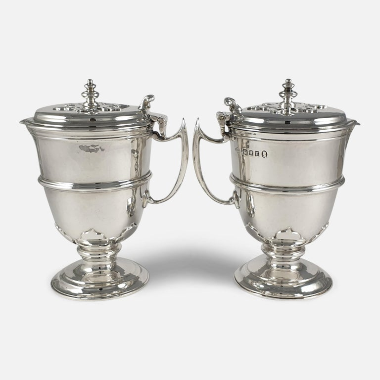 A pair of George V Arts and Crafts style sterling silver jugs. The planished jugs are of circular form, having hinged covers with disc finial and scroll thumb-piece. The body of the jugs have a central girdle and card-cut decoration in relief, with