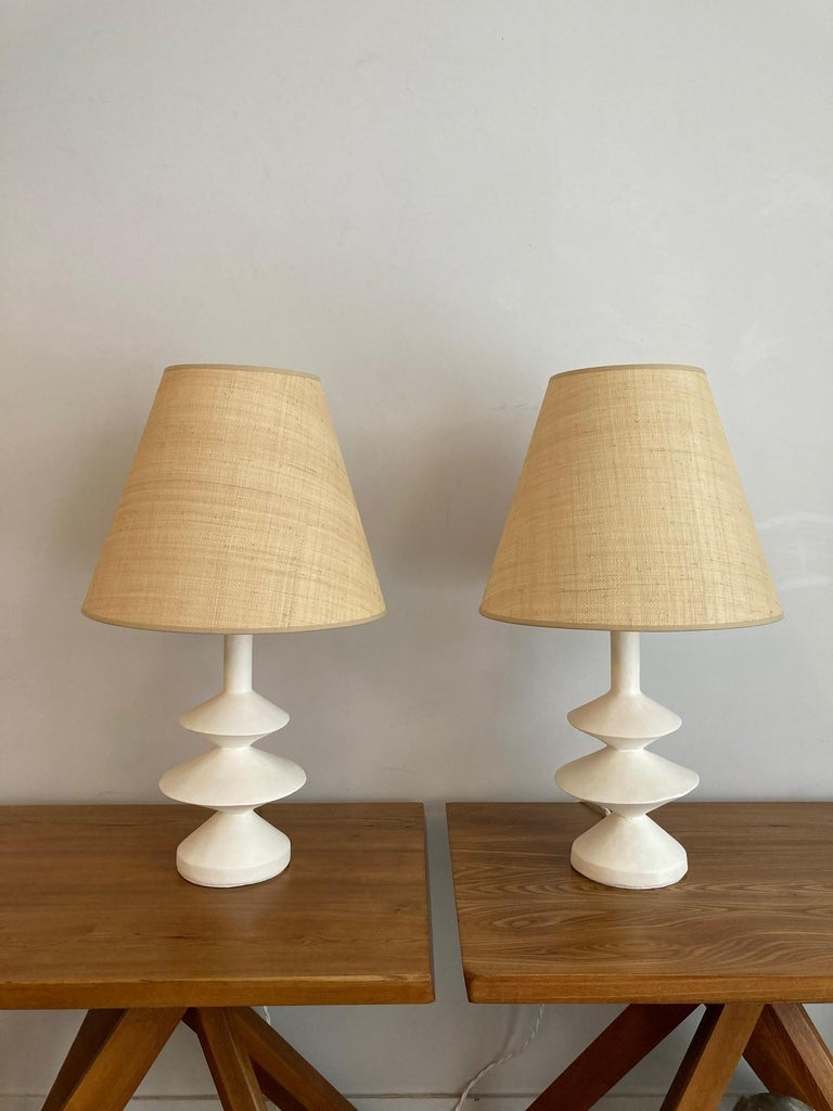Pair of plaster lamps and custom-made raffia shades  This production is inspired by the plaster lamp created by Giacometti for Jean-Michel Frank in the 30's.  French decorator Jacques Grange also designed a plaster lamp inspired by the Giacometti