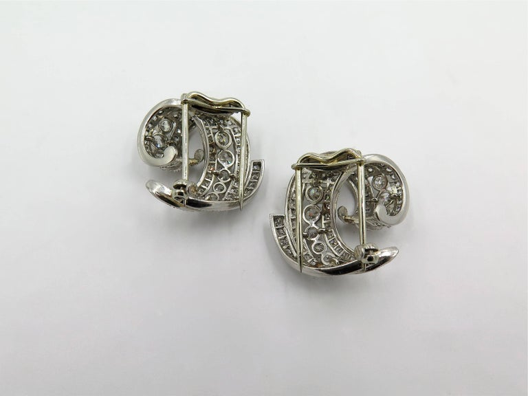 A pair of platinum and diamond brooches. Circa 1950. Each of scrolling design, set with circular and pave set diamonds. One hundred and forty six diamond weigh approximately 3.40 carats total. Length is approximately 1 inch. Gross weight is