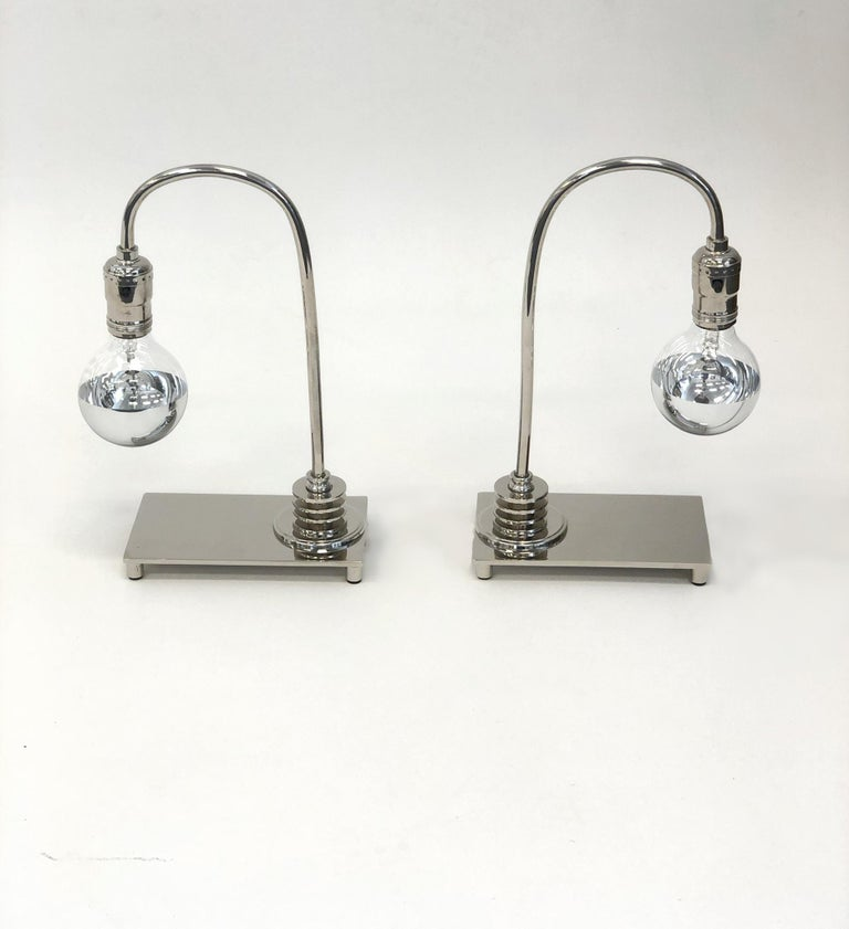 """A beautiful pair of polish nickel Art Deco table lamps. The lamps have been newly nickel-plated and rewired. The light bulbs are half chrome dipped bulbs. Dimension: 12.25"""" high, 8"""" wide, 4"""" deep."""