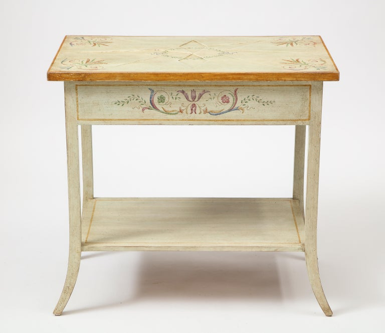 Pair of polychrome painted bedside tables of off-white / pale gray ground decorated with neoclassical bellflower garlands; the rectangular top centered by a recessed starburst and with gilt edge; fitted with one frieze drawer to the side; raised on