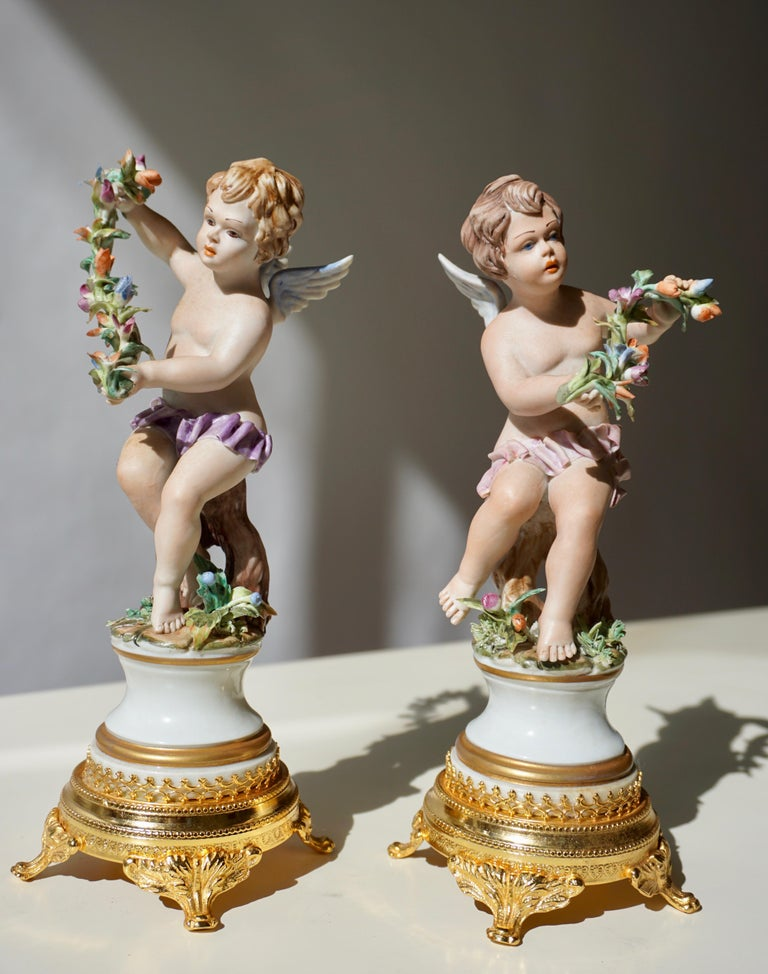 Pair of handmade polychrome porcelain sculptures depicting two winged angels, a pair of fine putti, one holding flowers, Allegory of abundance. Both porcelain figures stand on a golden circular brass base. In excellent condition, both putti figures