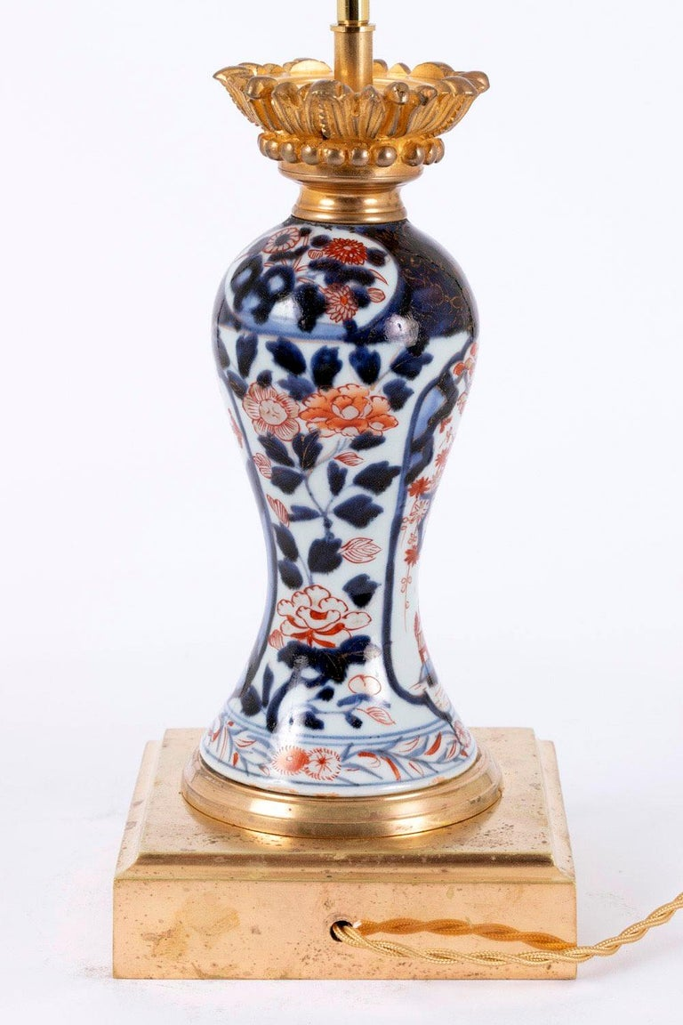 Pair of baluster shaped lamps in Imari porcelain. Chiselled and gilt bronze mount, standing on a moulded square shape base. Lamp body bottom part decorated with a frieze of blue edgings framing chrysanthemum and red foliage. Floral Imari decor, blue