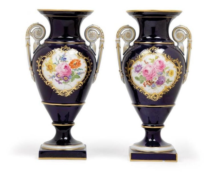 Pair of vases, porcelain, cobalt blue walls with fine and broad margins of gold, on the front a reserve with a colorfully painted bouquet on a white background, framed by golden leaves, white handles with golden edges, rosettes and leaves, round