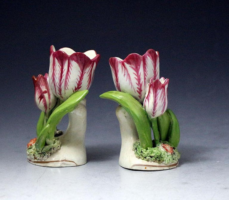 A highly decorative pair of tulip ornaments the main flower modelled with leaves and buds on a circular base with a single flower nestled on the grass.