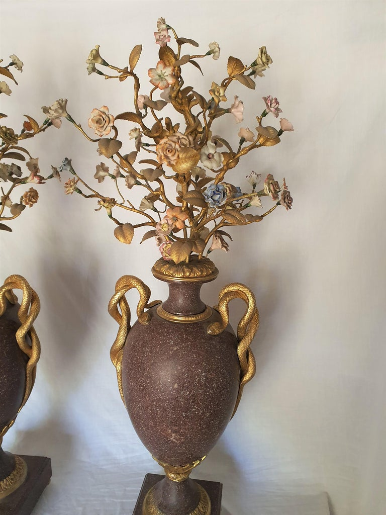 Rare and ancient pair of Egyptian porphyry vases with finely chiseled and gilded bronze applications, in the upper part, precious gilded bronze workmanship to compose branches and precious flowers in painted porcelain at the ends. Serpent handles