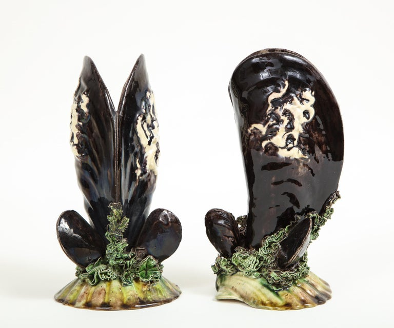 Unusually eccentric vases in the form of black mussel shells resting on a bed of seaweed and a scallop shell. Caldas da Rainhas factory mark on underside.