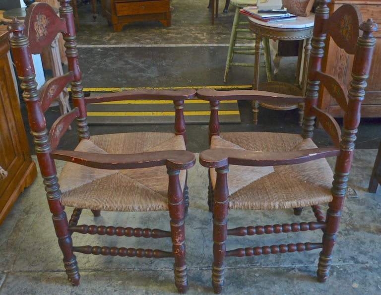 Pair of Portuguese 19th century hand painted ladder back armchairs with rush seat and painted flower motif.