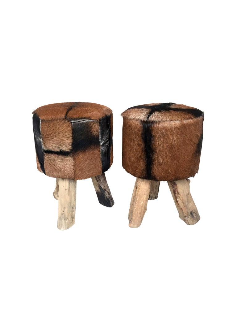 """Late 1970s pair of stools of African origin. Raw wood tripod base.   Priced for the pair.   Measures: 17.5"""" H x 11.5"""" D."""