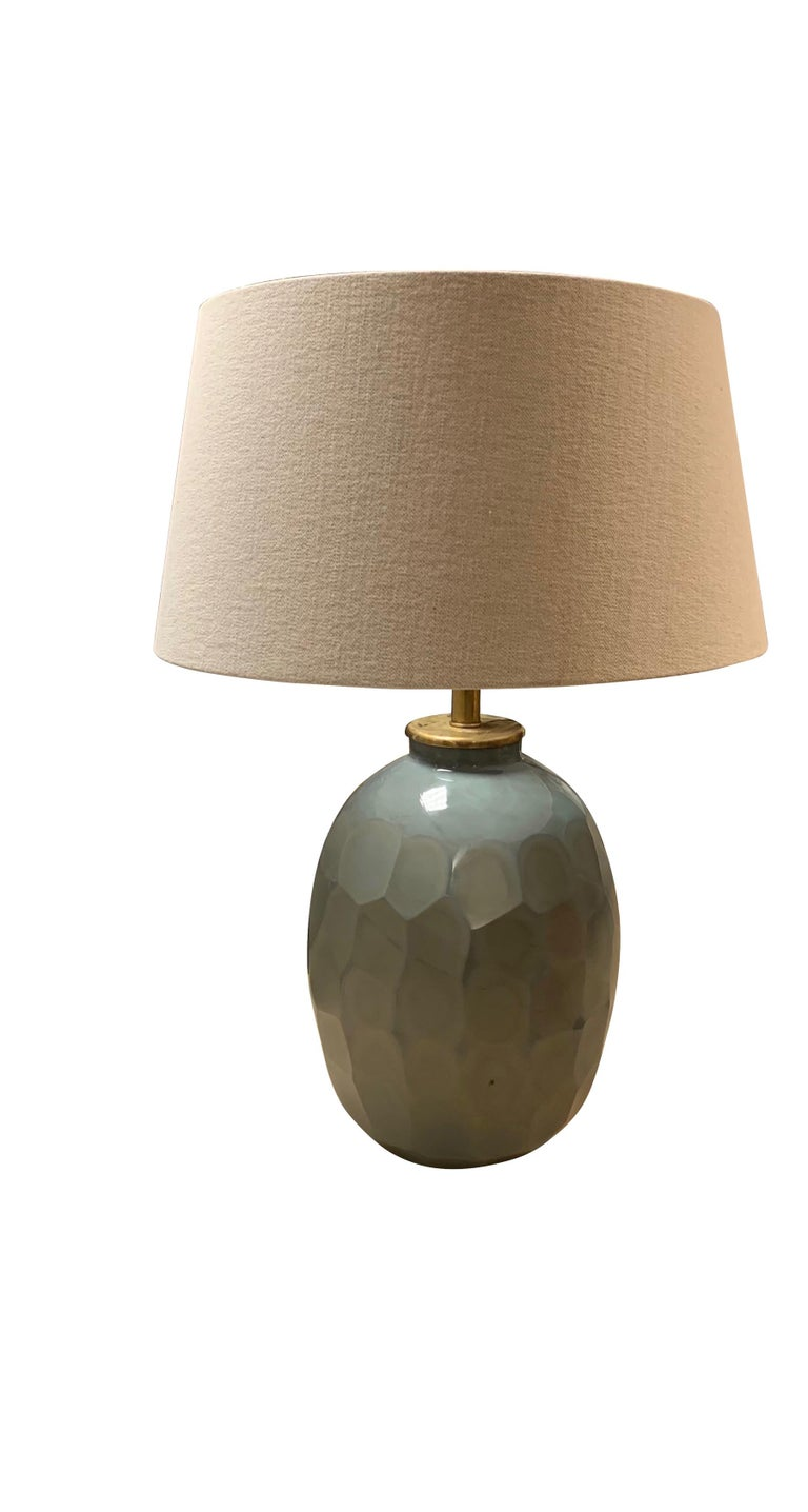 Contemporary Chinese pair of prism cut pale blue glass lamps. The prism cut glass creates a honeycomb pattern. Belgian linen shades Measures: Overall height 29