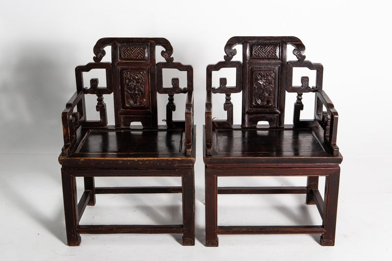 These handsome elm chairs feature floral and cloud scroll pattern carvings. Dating to the Qing Dynasty, the chairs are made up of two parts: a waisted stool and an upper back-rest that resembles a screen panel. Stout and with a generous cut, these