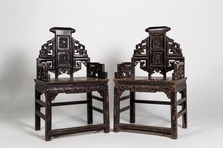These handsome chairs feature intricate carvings depicting dragons, steeped arms and an ornate scroll on its crest rail. Made from the Qing dynasty, the chairs are made up of two parts: a waisted stool and an upper backrest that resembles a screen