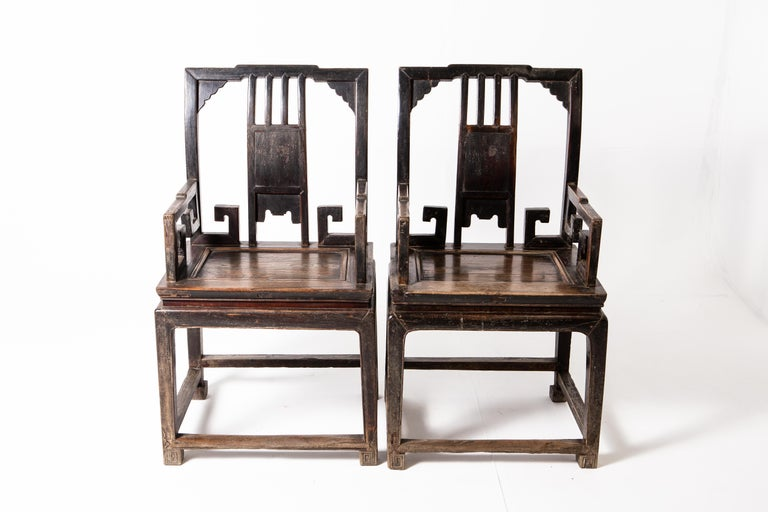 These handsome chairs are from the mid-Qing dynasty period and they feature unique scroll carvings under the armrest. The chair is made of two parts: a waisted stool and an upper backrest that resembles a screen panel. Stout and with a generous cut,