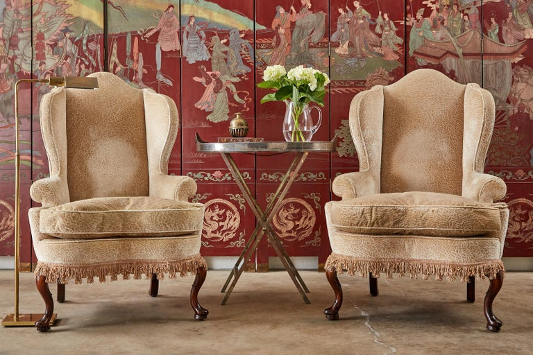 Distinctive pair of upholstered wing chairs by Dunbar. The wingbacks feature a hardwood frame with tall peaked crests and fully developed wings. The chairs are crafted in the Queen Anne taste with cabriole legs in the front ending with pad feet. The