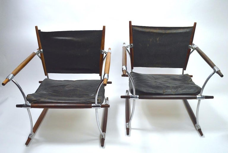 Rare and important pair of Safari chairs designed by Jens Quistgaard for Dansk Danmark. Both chairs are structurally sound and sturdy, both show significant wear to the black leather upholstery, including tears to the back rest slings, as shown.