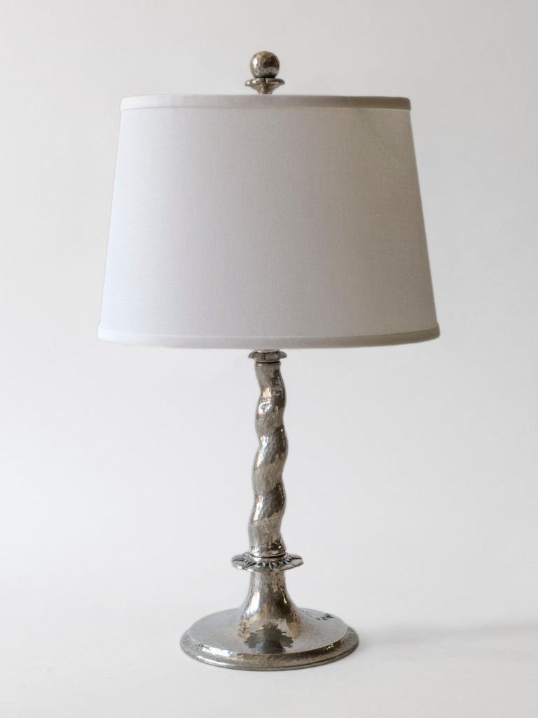 Each finial depicting a raised globe on a hourglass shaped blossom, surmounting a barley-twist stem, resting on a stylized rosette, terminating in a circular foot.   Each lamp hammered throughout and with minor handmade differences. The overall