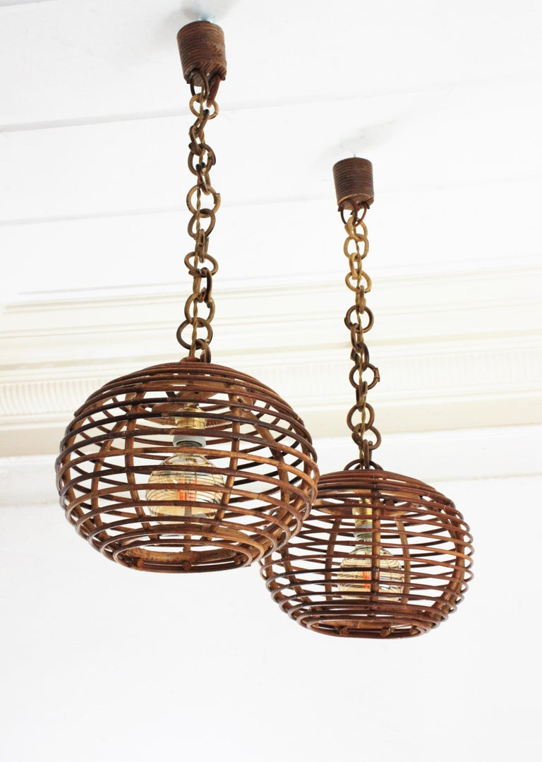 Eye-catching pair of rattan lanterns with globe or ball shaped lampshades, Spain, 1950-1960s. These suspension lamps are entirely handcrafted with rattan, bamboo and wicker. The ball shaped shades hang from chains with round rattan links that can